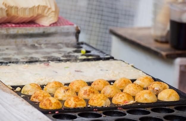 Proces gotowania kulki takoyaki na gorącej patelni.takoyaki to najbardziej znane japońskie przekąski w japonii.