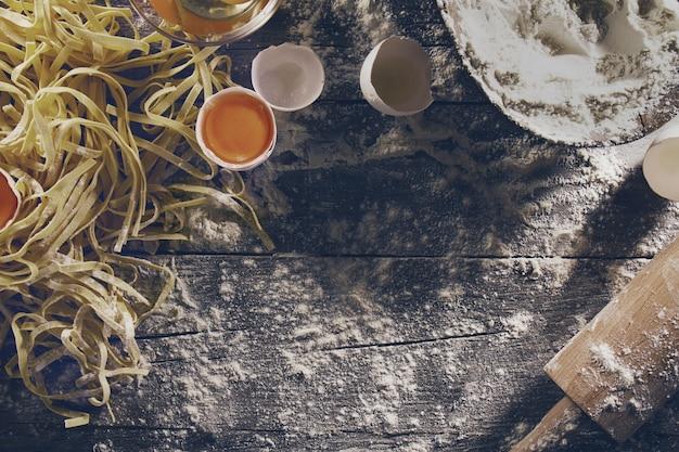 Proces gotowania makaronu ze świeżymi surowcami do klasycznego włoskiego jedzenia - surowe jaja, mąka na drewnianym stole. widok z góry. tonowanie.