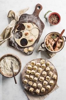 Proces gotowania pierogów. wiele gotowych pierogów wieprzowych na dużej drewnianej desce z mąką na jasnym tle.