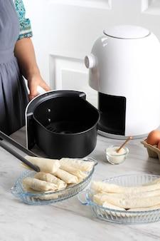 Proces gotowania przy użyciu białej frytownicy do zdrowego gotowania w kuchni. kobieta ręcznie wkłada placki/lumpia do tacy do frytownicy powietrznej