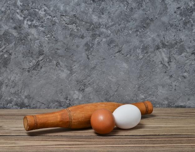 Proces gotowania wałek do ciasta, jajka na drewnianej półce na betonowej ścianie