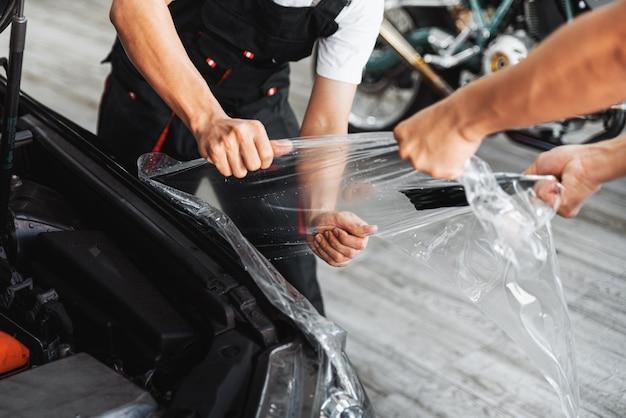 Proces instalacji ppf, ręczne rozciąganie, usuwanie starej przezroczystej folii na reflektorze i pokrywie samochodu ręcznie. profesjonalna usługa motoryzacyjna.