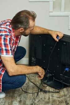 Proces instalacji złota rączka patrząca skupiona na trzymaniu kabla telewizyjnego podczas instalacji lub mocowania telewizora