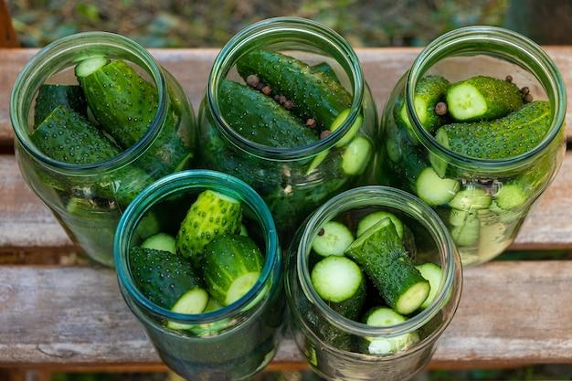 Proces konserwowania korniszonów, ogórków kiszonych w szklanych słoikach.