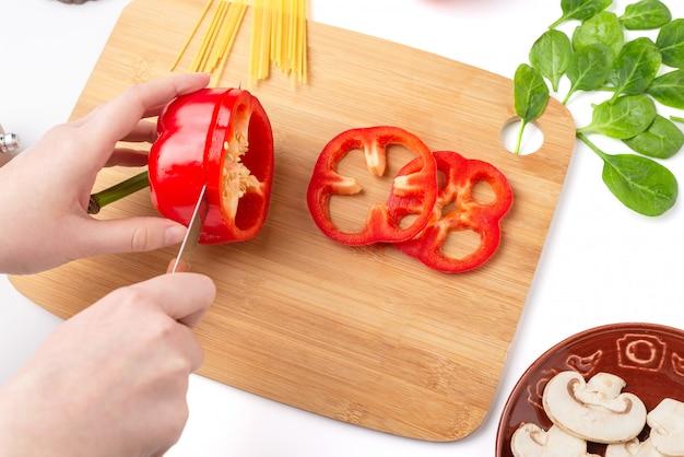 Proces krojenia papryki. pieczarki, liście szpinaku, spaghetti na białym tle.