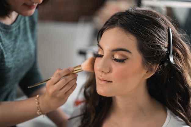 Proces makijażu dla pięknej kobiety