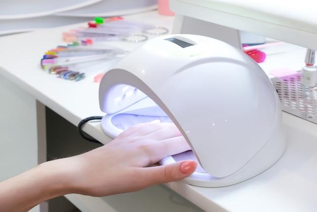 Proces manicure hybrydowego w lampie uv. procedura salonowa. mistrz pokrywa paznokcie klientów szelakiem