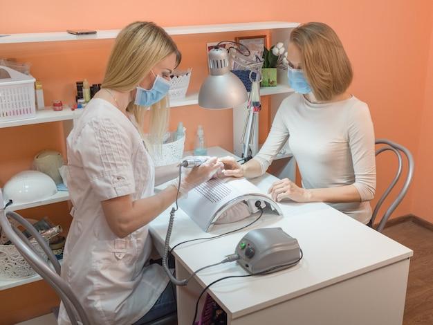 Proces manicure, manicure sprzętowy. leczenie obcinaków do paznokci. pracuj w masce medycznej, ochrona przed pandemią