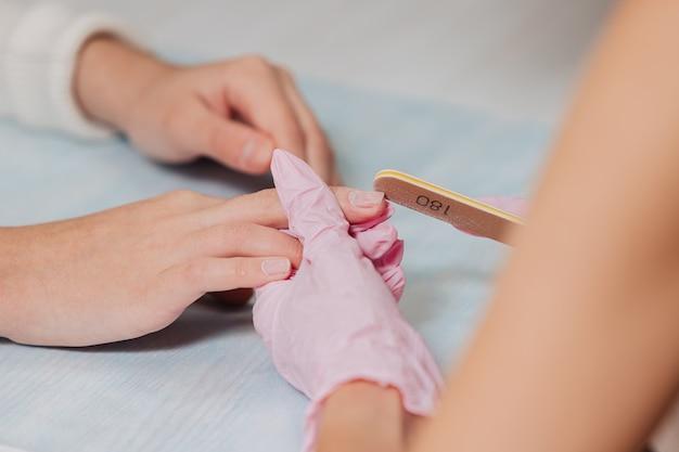 Proces manicure. mistrz w różowych gumowych rękawiczkach przetwarza paznokcie pilnikiem do paznokci. kobiece ręce z bliska.