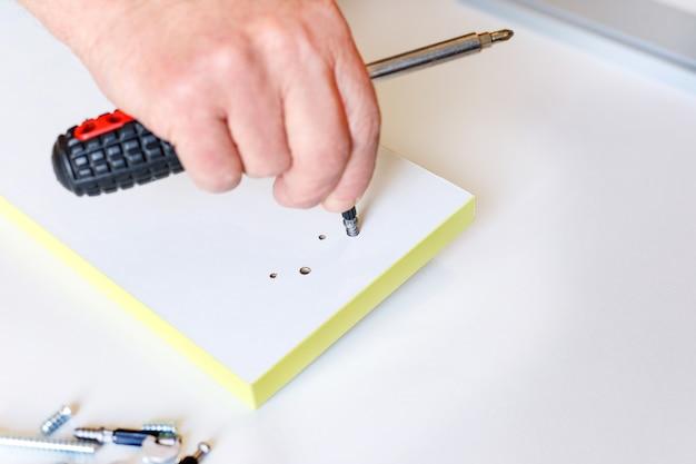 Proces montażu łączników na elewacji szuflady meblowej.