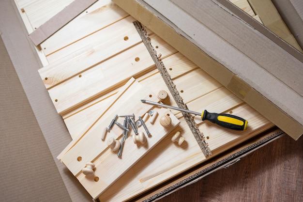 Proces montażu mebli drewnianych. śruby i śrubokręt na częściach drewnianych.