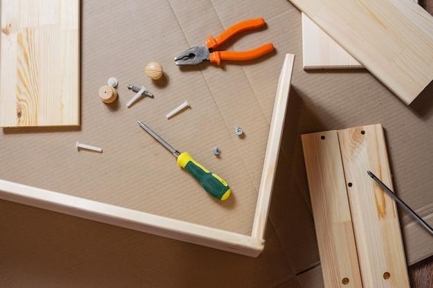 Proces montażu mebli drewnianych. śruby, śrubokręt, szczypce i elementy drewniane.