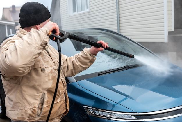 Proces mycia samochodu wodą pod wysokim ciśnieniem.