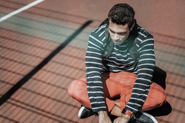 Proces myślenia. zamyślony facet opuszczający ramiona i siedzący na ziemi