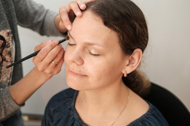 Proces nakładania makijażu na twarz europejki