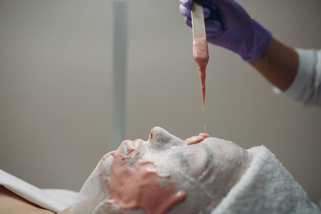 Proces nakładania maski alginianowej. kobiece ręce kosmetyczki trzymającej szpatułkę. kobieta leżąc na kanapie w gabinecie kosmetologa. pielęgnacja twarzy w salonie kosmetycznym spa.