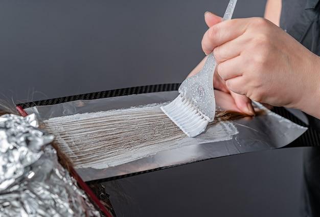 Proces nakładania na włosy pudru rozjaśniającego i owinięcia folią. technika szatusz