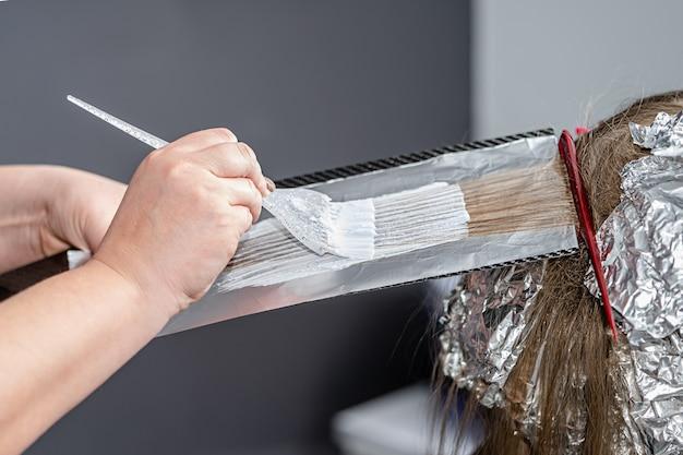Proces nakładania proszku rozjaśniającego na włosy klienta i zawijania w folię. technika shatush