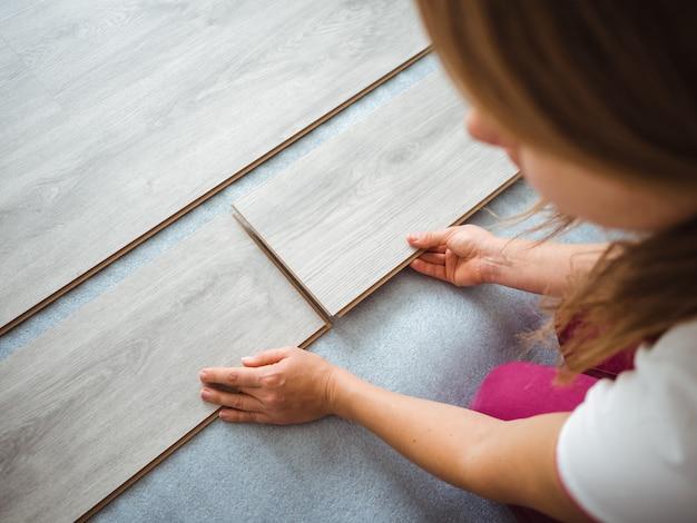 Proces naprawy w mieszkaniu. dziewczyna kładzie laminat na podłodze. widok z tyłu