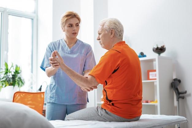 Proces odzyskiwania. przyjemny starszy mężczyzna podnoszący rękę podczas masażu