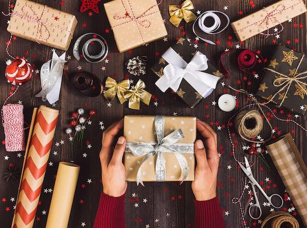 Proces opakowania świąteczne pudełko mężczyzna w ręku trzyma pudełko na nowy rok