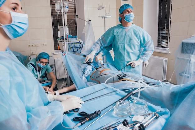 Proces operacji chirurgii ginekologicznej przy użyciu sprzętu laparoskopowego. grupa chirurgów w sali operacyjnej ze sprzętem chirurgicznym