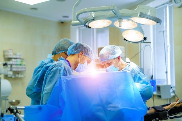 Proces operacji chirurgii urazowej. grupa chirurgów w sali operacyjnej ze sprzętem chirurgicznym. wykształcenie medyczne, selektywne skupienie