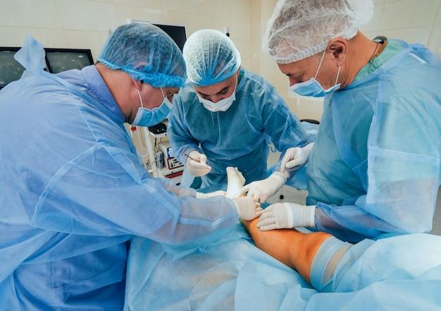 Proces operacji chirurgii urazowej. grupa chirurgów w sali operacyjnej ze sprzętem chirurgicznym.