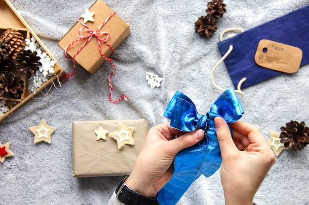 Proces pakowania prezentów. niebieska kokarda. prezenty w papierze rzemieślniczym. świąteczna atmosfera. wystrój noworoczny. minimalistyczne opakowanie na prezent