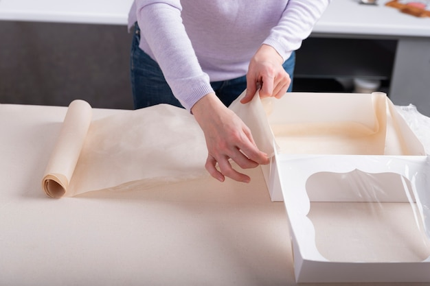 Proces pakowania prezentów w białe pudełko kartonowe. cukiernik pakuje słodycze.