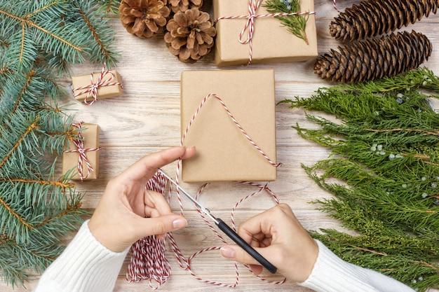 Proces pakowania pudeł z prezentami świątecznymi. widok z góry