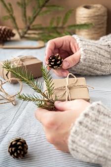 Proces pakowania stylowych nowoczesnych prezentów na boże narodzenie i nowy rok. pudełka na prezenty wykonane z papieru kraft, sznurka i gałązek choinkowych. boże narodzenie tło, wakacyjna atmosfera.