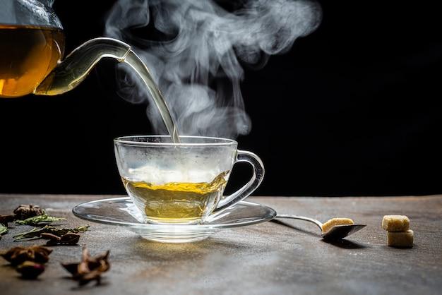 Proces parzenia herbaty, filiżanka świeżo parzonej herbaty owocowej i ziołowej, ciemny nastrój.