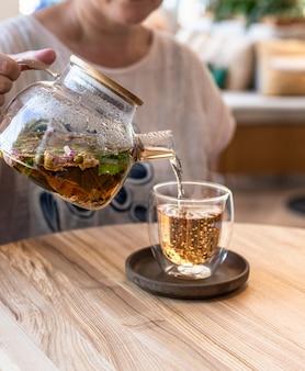 Proces parzenia herbaty. gorąca herbata ziołowa lub zielona z miętą i płatkami róży. selektywne skupienie.