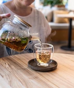 Proces parzenia herbaty. gorąca herbata ziołowa lub zielona z miętą i płatkami róży.