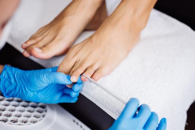 Proces pedicure pedicure w salonie domowym pielęgnacja stóp i paznokci proces profesjonalnego pedicure mistrz w niebieskich rękawiczkach wykonuje pedicure