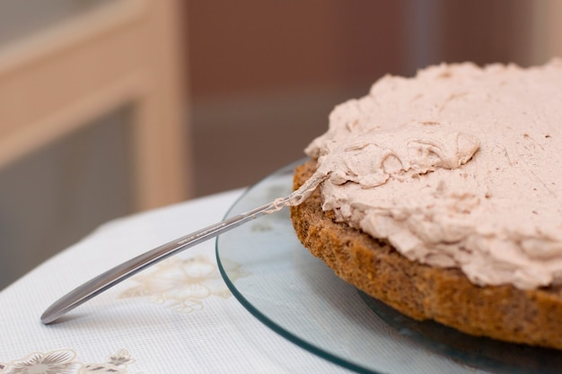 Proces pieczenia ciasta w domu. zbliżenie na herbatniki czekoladowe w plasterkach ze śmietaną. koncepcja kulinarne i pyszne desery.