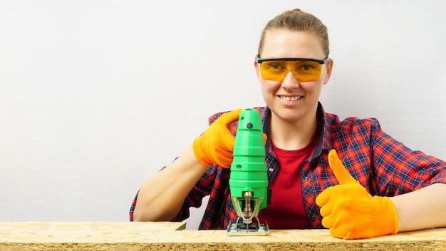Proces piłowania sklejki wyrzynarką, kobieta trzyma w dłoni narzędzie, pokazuje kciuk do góry, kopiuje miejsce