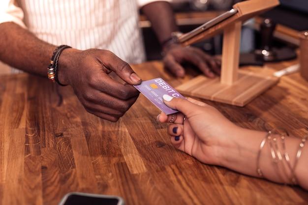 Proces płatności. miły młody człowiek stojący przy kasie podczas płatności kartą debetową