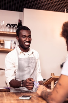 Proces płatności. pozytywny miły człowiek wyciąga rękę podczas przyjmowania płatności