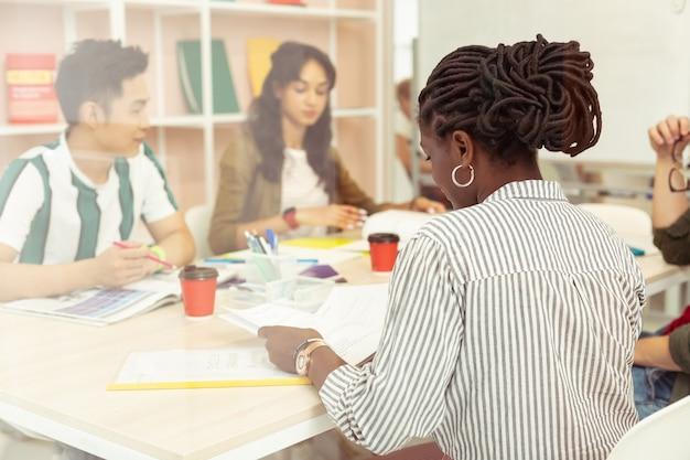 Proces pracy. grupa międzynarodowych studentów siedzących w klasie i ćwiczących język obcy