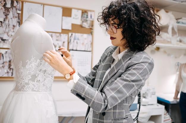 Proces pracy krawca w jej pracowni projektantka mody szyje suknię ślubną przypinając koronkę do manekina