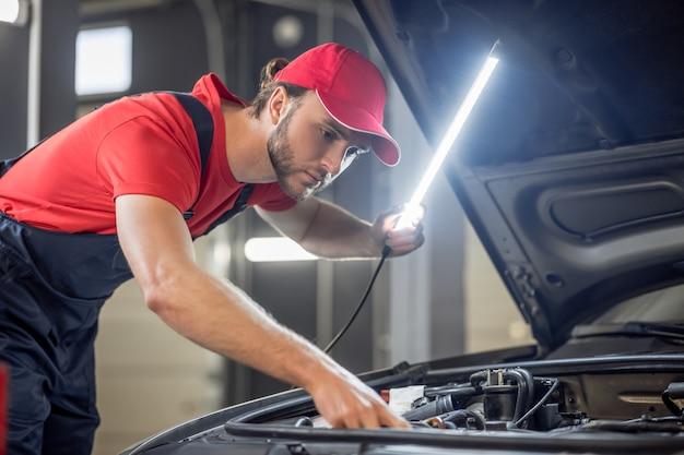 Proces pracy. młody, brodaty mechanik samochodowy w czerwonej koszulce i czapce z lampką sprawdzająca anatomię samochodu pod maską