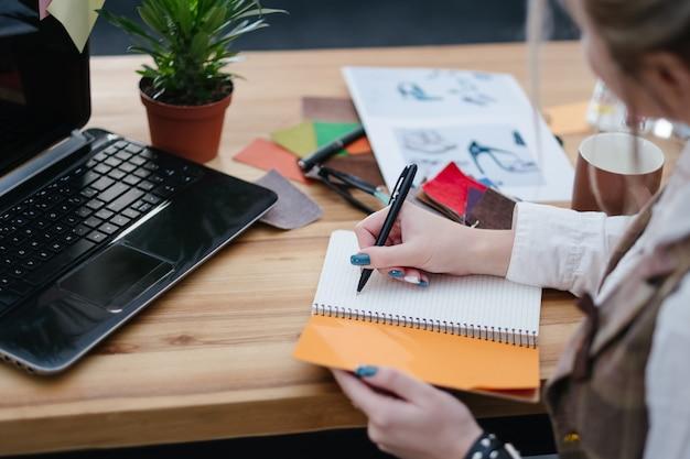 Proces pracy projektanta mody. biurko z próbkami kolorów szkiców i materiałów eksploatacyjnych na stole. kobieta pisząca notatki i pomysły w swoim notatniku