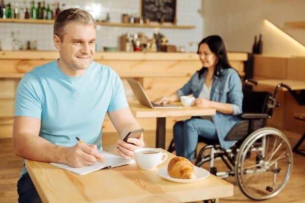 Proces pracy. przystojny, wesoły dobrze zbudowany blondyn trzyma telefon i pisze w swoim zeszycie, podczas gdy kobieta siedzi na wózku inwalidzkim w tle