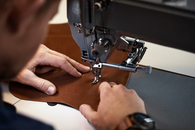 Proces pracy rzemieślnika skórzanego. garbarz lub skinner szyje skóry na specjalnej maszynie do szycia, z bliska.pracownik szyje na maszynie do szycia.