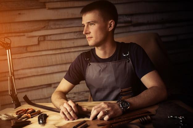 Proces pracy skórzanego paska w warsztacie skórzanym. mężczyzna trzyma wykonywać ręcznie narzędzie i działanie. garbarnia w starej garbarni. drewniana powierzchnia stołu. ciepłe światło dla tekstu i projektu