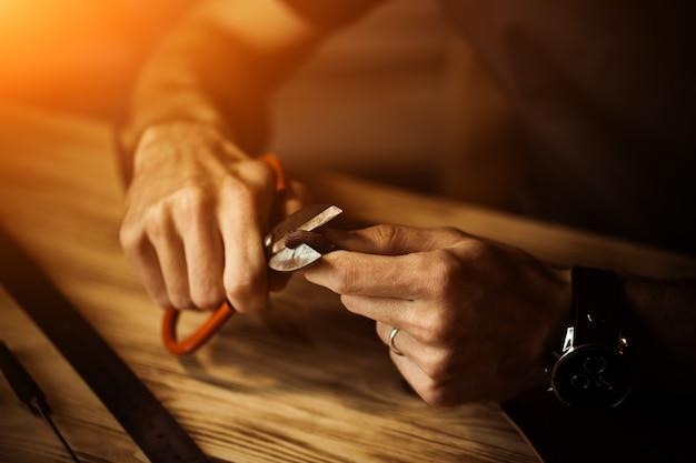Proces pracy skórzanego paska w warsztacie skórzanym. mężczyzna trzyma wykonywać ręcznie narzędzie i działanie. garbarnia w starej garbarni. drewniana powierzchnia stołu. ramię człowieka z bliska. ciepłe światło dla tekstu i projektu