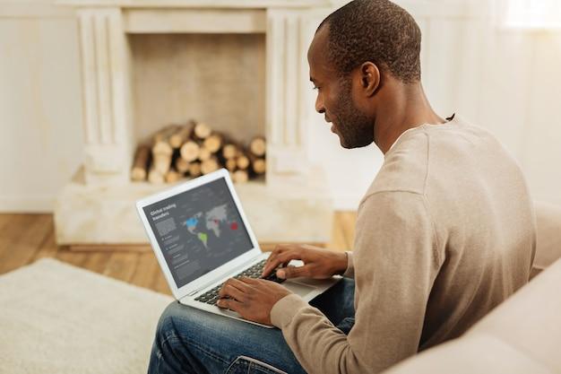 Proces pracy. szczęśliwy ciemnooki afroamerykański mężczyzna uśmiecha się i pracuje na laptopie, siedząc na kanapie i kominkiem w tle