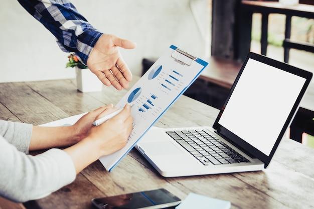 Proces pracy w zespole. młoda załoga business managerów pracujących z nowym projektem startupowym. labtop na stole drewna, pisania na klawiaturze, wiadomości sms, analizować plany wykresów